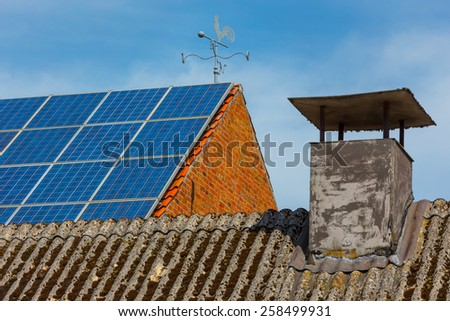 Very old corrugated chimney roof in the foreground in focus. Tiles roof with weather vane and solar battery out of focus in background - stock photo