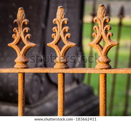 Very old decorative wrought iron fence in a cemetery - stock photo