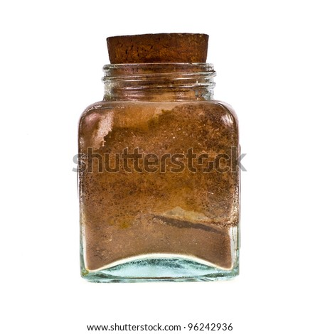 Very old glass jar with cinnamon inside on white background - stock photo