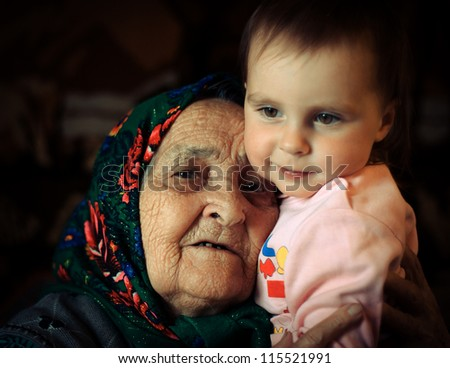 Very old grandmother lovingly embraces his granddaughter