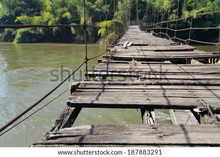 very old hanging footbridge across river. - stock photo