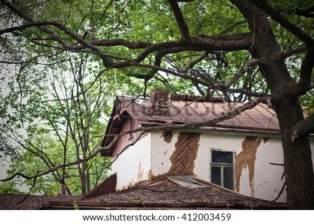Very old house in the forest round trees. Summer, sunny day. - stock photo