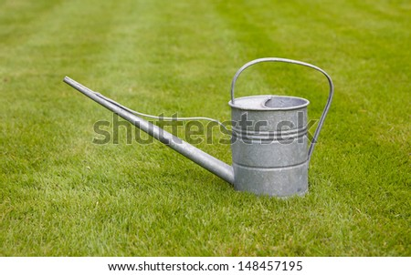Very old metal watering-can on a green field - stock photo