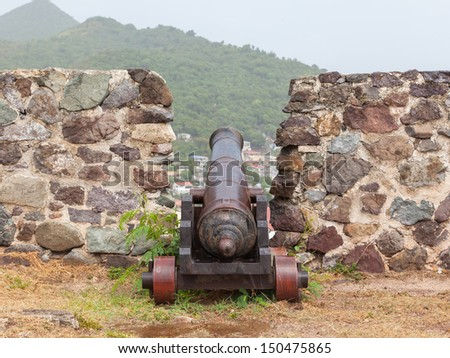 Very old rusted canon on top of an old wall, Caribbean - stock photo