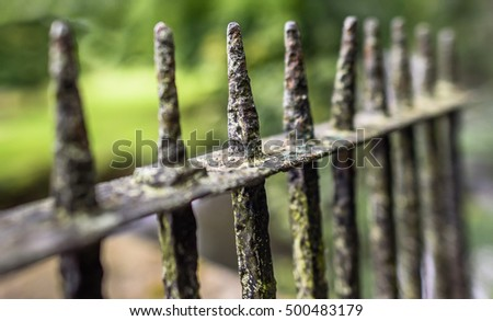 Very old, rusty spikes on a cast iron railing.