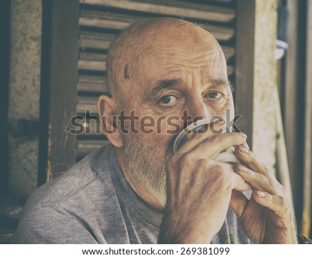 Very old senior man drinking coffee / tea. Analog effected photo.