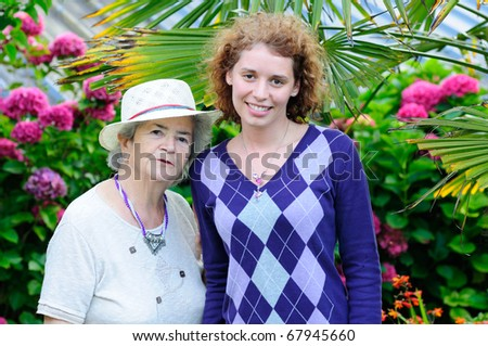 Very old senior woman and young woman smiling in garden - stock photo