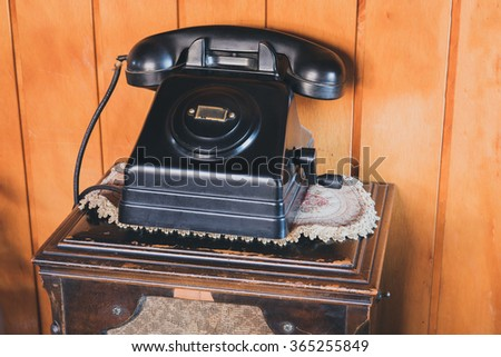 Very old telephone in a wooden background - stock photo