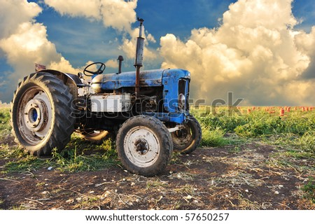 Very old tractor in field, different parts - no trademark at all - stock photo