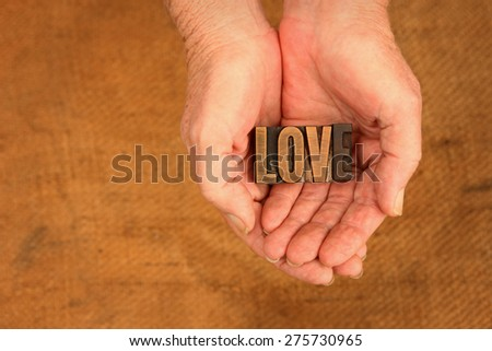Very Old Vintage Letterpress letters in hands spelling out Love - stock photo