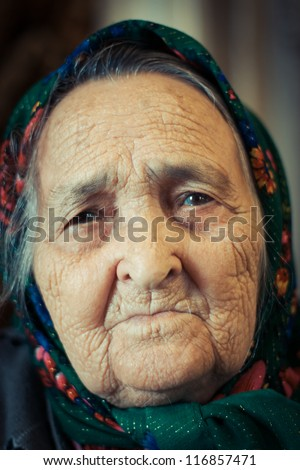 Very old woman alone in a scarf. - stock photo