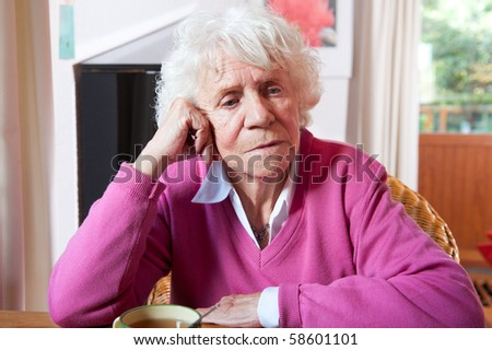 Very old woman in sitting at the table with cup of tea