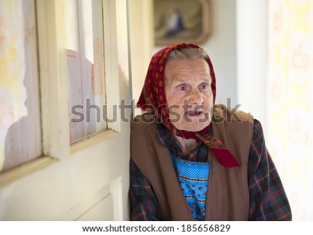 Very old woman is standing by the door and looking to the camera at her country style house - stock photo