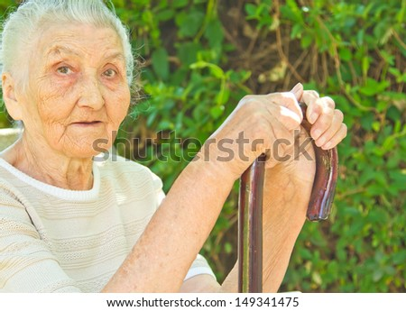very old woman sitting in the park and standing against a walking stick - stock photo