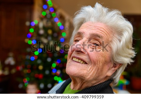 Very old woman sitting near a christmas tree