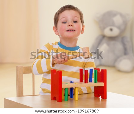 very passionate about intelligent boy with great pleasure scores plastic hammer nails. - stock photo