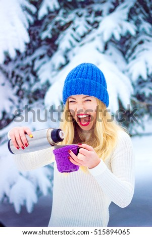 very positive woman pours tea in  winter park . Young woman winter portrait.