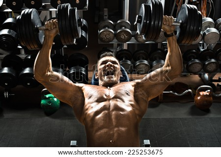 very power athletic guy bodybuilder ,  execute exercise press of dumbbells on pectoral muscle, in gym - stock photo