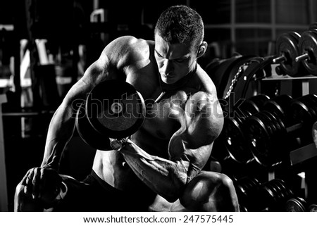 very power athletic guy bodybuilder ,  execute exercise with  dumbbells, in dark gym, black and white photo - stock photo