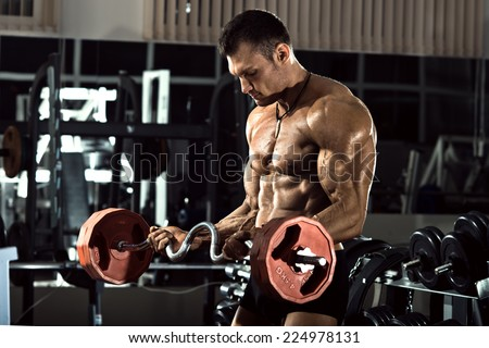 very power athletic guy bodybuilder ,  execute exercise with  with  weight, in dark gym - stock photo
