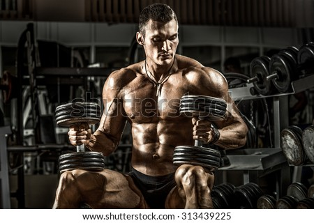 very power athletic guy bodybuilder , sit with  dumbbells, in dark gym - stock photo