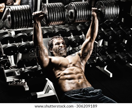 very power athletic guy ,  execute exercise press with  dumbbells, in gym