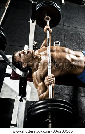 very power athletic guy ,  execute exercise press with weight, in gym - stock photo