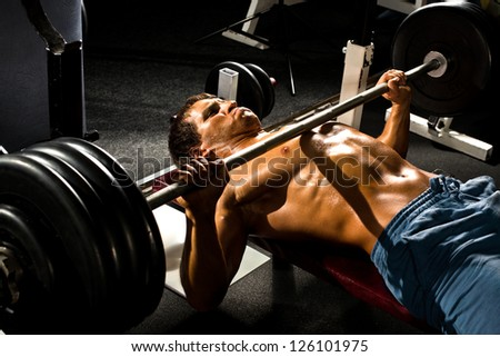 very power athletic guy ,  execute exercise press with weight, in sport hall - stock photo