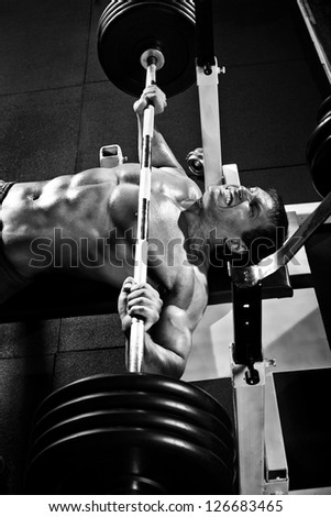 very power athletic guy ,  execute exercise press with weight, in sport hall, black-and-white photo - stock photo