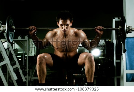 very power athletic guy ,  execute exercise with  dumbbells, in  sport-hall - stock photo