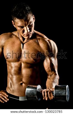 very power athletic guy ,  execute exercise with  dumbbells, on bkack background - stock photo