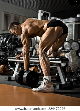 very power athletic guy ,  execute exercise with  dumbbells, on bkack background - stock photo