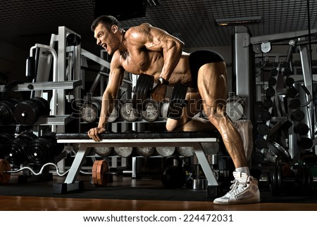 very power athletic guy ,  execute exercise with  dumbbells, on broadest muscle of back - stock photo