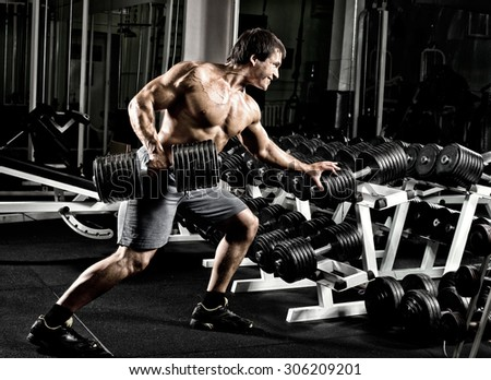 very power athletic guy ,  execute  traction with  dumbbells, exercise on broadest muscle of back, in gym