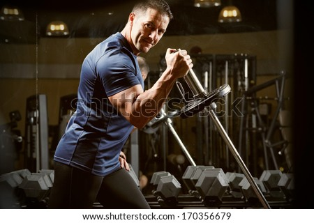 very power athletic guy , execute traction with dumbbells, exercise on broadest muscle of back, in sport hall