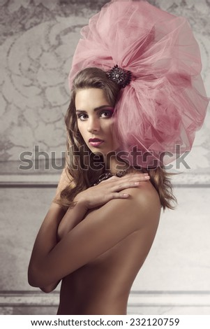 very pretty brunette girl wearing stylish big tulle accessory in the hair, posing naked and covering her breast  - stock photo