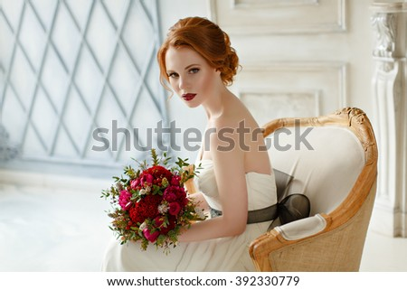Very pretty sophisticated red-haired girl sitting in a chair with a bouquet in hand, in the interiors of the studio