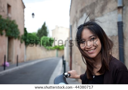 Very pretty young asian woman on bike smiling while commuting/biking to work - stock photo