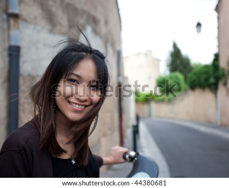 Very pretty young asian woman on bike smiling while on her back home from work on a city street - stock photo