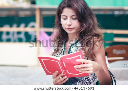 very pretty young woman reading a book