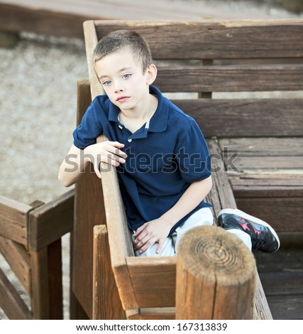 Very sad handsome boy sitting in the park  - stock photo