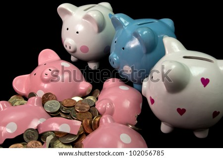 Very sad piggy banks looking at broken friend - stock photo
