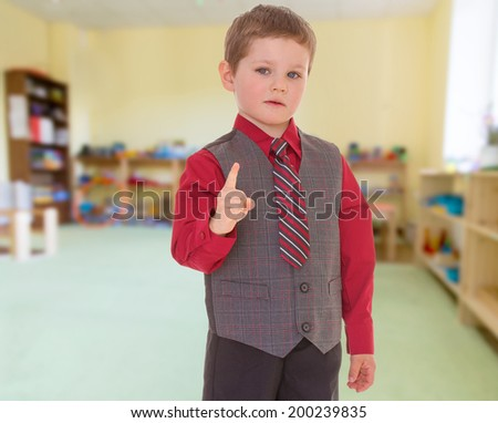 very serious little boy in a suit and tie shakes his finger