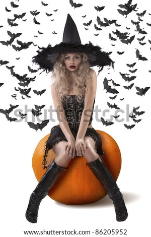 very sexy and attractive blond witch with a black feather hat and sitting on a pumpkin