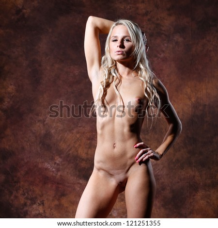 very sexy and beautiful nude or naked woman with blond long hair is posing in front of a brown flamed textured  background - stock photo