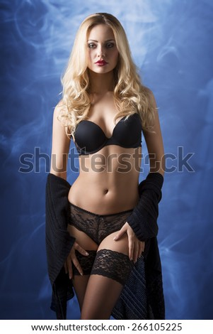 very sexy blonde woman with long hair and stylish make-up wearing black lingerie and lace stockings, in sensual pose with fit body  - stock photo