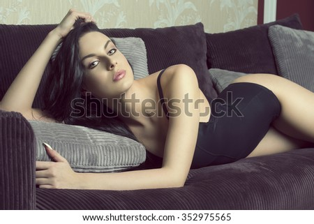 very sexy brunette female with perfect slim body and black lingerie, in sensual pose on velvet sofa  - stock photo