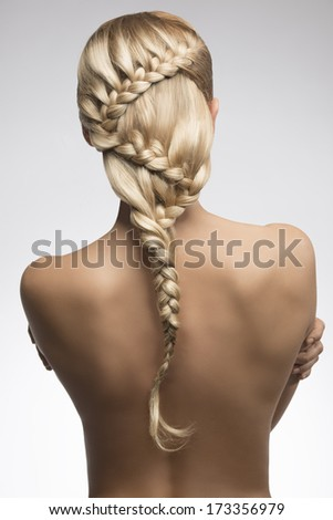 very sexy girl with long braid creative hair-style turned on her sensual naked back  - stock photo