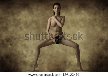 very sexy nude girl brunette hides her pubis with camera and looking in camera - stock photo