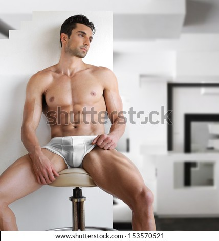Very sexy young fit man in white underwear in modern contemporary interior setting - stock photo